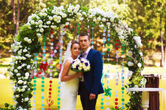 Married couple in flower arch royalty free stock image