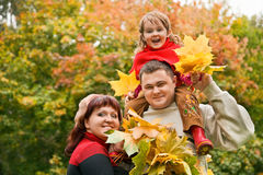 Married couple and girl collect leafs In park Stock Photos