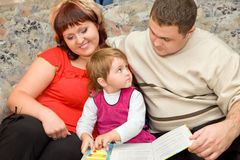 Married couple and girl read book in cosy room Royalty Free Stock Image