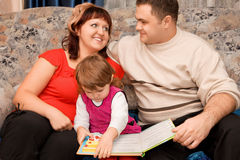 Married couple and girl read book in cosy room Stock Images
