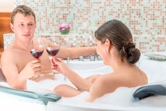 Married couple with glasses of wine in the jacuzzi Stock Photos