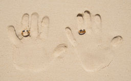 Hand print on sand with wedding rings. Hand print of married couple with wedding rings on sand.Wedding travel, beach marriage, honeymoon, beach wedding Stock Images