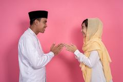 Married couple hand touching muslim forgiving. Over pink background royalty free stock image