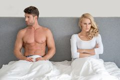 Married couple having an argument. Sitting up n their bed facing off in opposite directions as they ignore one another Royalty Free Stock Photography