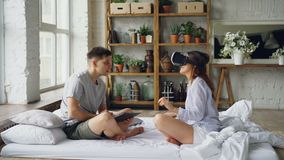 Married couple is having fun with augmented reality glasses, young woman is wearing then and smiling moving hands and. Her husband is using tablet. Modern stock video footage