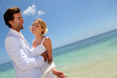 Married couple having fun at the beach. Bride and groom dancing by blue lagoon Royalty Free Stock Photos