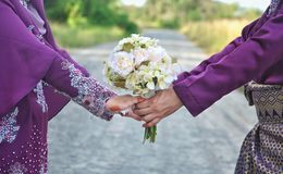 Married couple holding hand. Closeup view of married couple holding hands and carrying bride`s bouquet Royalty Free Stock Photo