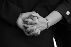 Married Couple Holding Hands. A working man's hands with his wife at their sons wedding Royalty Free Stock Image