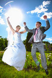 Married couple holding hands and jumping high at the park Stock Photography