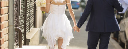 Married couple holding hands on street.  Stock Photo
