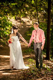Married couple holding hands and walking at park Stock Photo