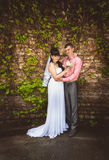 Married couple hugging against old brick wall Royalty Free Stock Photo