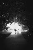 Married couple hugging in tree tunnel at park Stock Photography