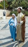 A married couple - husband and pregnant wife in the clothes of Jesus` time - stand in front of the Basilica of the Annunciation in. Nazareth, Israel, December 23 stock images