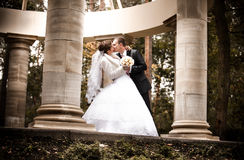 Married couple kissing in alcove with columns Royalty Free Stock Photo