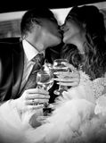Married couple kissing in car while holding glasses of champagne Stock Images
