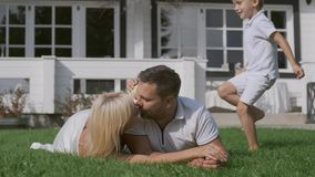Married couple kissing lying on the grass. Children play and run near them. Young married couple kissing while lying on the grass. Children play and run near stock footage