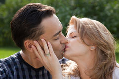Married couple kissing outdoors stock photo