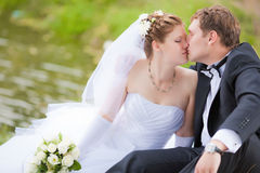 Married couple kissing in park. The newly married couple kissing in park Stock Images
