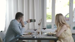 Married couple in a light restaurant and photographed on a smartphone. Married couple have supper in a light restaurant and photographed on a smartphone. Man in stock footage