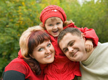 Married couple and little girl in park in autumn Stock Photos