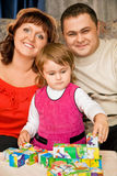 Married couple and little girl playing cubes Royalty Free Stock Photo