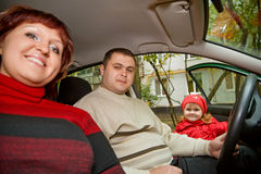 Married couple and little girl sit in car Stock Images