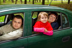 Married couple and little girl sit in car in park Stock Images