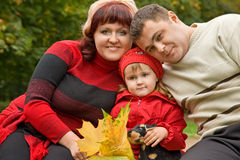 Married couple and little girl sit in park, autumn Stock Image