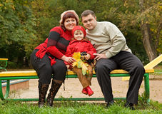 Married couple and little girl sit in park, autumn Royalty Free Stock Photography
