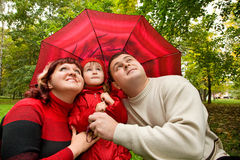 Married couple and little girl with umbrella Stock Photography