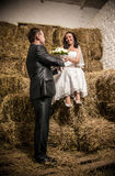 Married couple looking at each other at stable with stack of hay Royalty Free Stock Photography