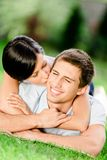 Married couple lying on the grass embraces each other Stock Photo