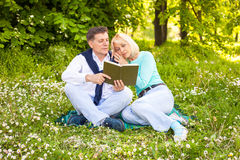 Married couple in the park. Senior couple reading a book in the park Royalty Free Stock Photos