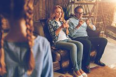 Married couple with phones ignoring their child. Lack of love. Selective focus on totally absorbed in their smartphones husband and wife relaxing on a sofa and Royalty Free Stock Photo
