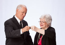 Married Couple Pinching a Penny for Retirement. Retirement aged married couple are pinching a penny (actually a $1 coin) on white background. The husband and Royalty Free Stock Photos