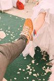 Married couple in plimsolls on green carpet Royalty Free Stock Images