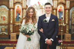 Married couple posing in a church after ceremony Royalty Free Stock Images