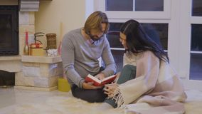 Married couple read the book near fireplace. Married couple sits on floor near fireplace and relaxing with book. Husband read the book to his wife. Happy man and stock video