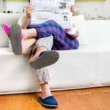Married couple reading newspaper dressed in pajamas sitting in s Stock Photography