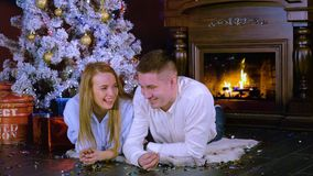 A young couple talks and plays with Christmas confetti on the floor. New year celebration concept. A married couple rests under a Christmas tree beside a stock video