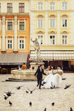 Married couple run across the citysquare full of pigeons.  Stock Photo
