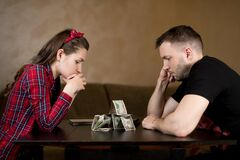 Married couple sadly looks at a house, folded on a table from cash savings