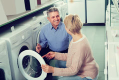 Married couple selecting home modern washing machine. Mature married couple selecting home modern washing machine in household appliances shop Royalty Free Stock Photo