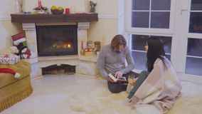 Married couple relaxing near fireplace and reads the book. Married couple sits on floor near fireplace and relaxing with book. Husband read the book to his wife stock video footage