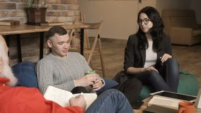 Young woman talks with husband at psychologist`s reception. Married couple sits on the sofa in bean bags at a psychologist`s reception. People tells about their stock video
