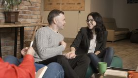 Young couple talks with psychologist at the reception. Married couple sits on the sofa in bean bags at a psychologist`s reception. People tells about their stock video