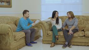 Married couple are talking with psychologist. Married couple sits on the sofa in the room at a psychologist`s reception. The psychologist looks through the stock video footage