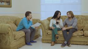 Husband and wife blames each other at the psychologist`s reception. Married couple sits on the sofa in the room at a psychologist`s reception. The woman blames stock video