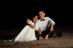 Married couple sitting on beach sand Stock Photos